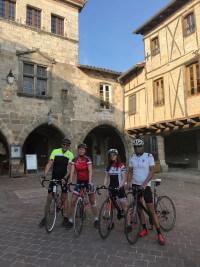 Four cyclists in the centre of Castelnau de Montmiral.
