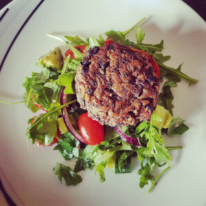 Hearty mushroom burger with vibrant green salad.