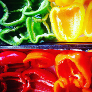 Roasted, green and yellow red peppers on a baking tray.