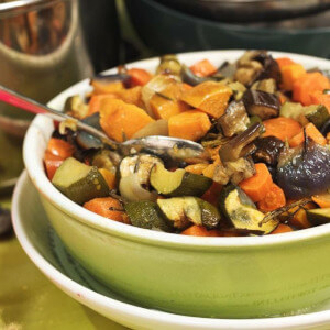 Roasted vegetable salad in a large green ceramic bowl.